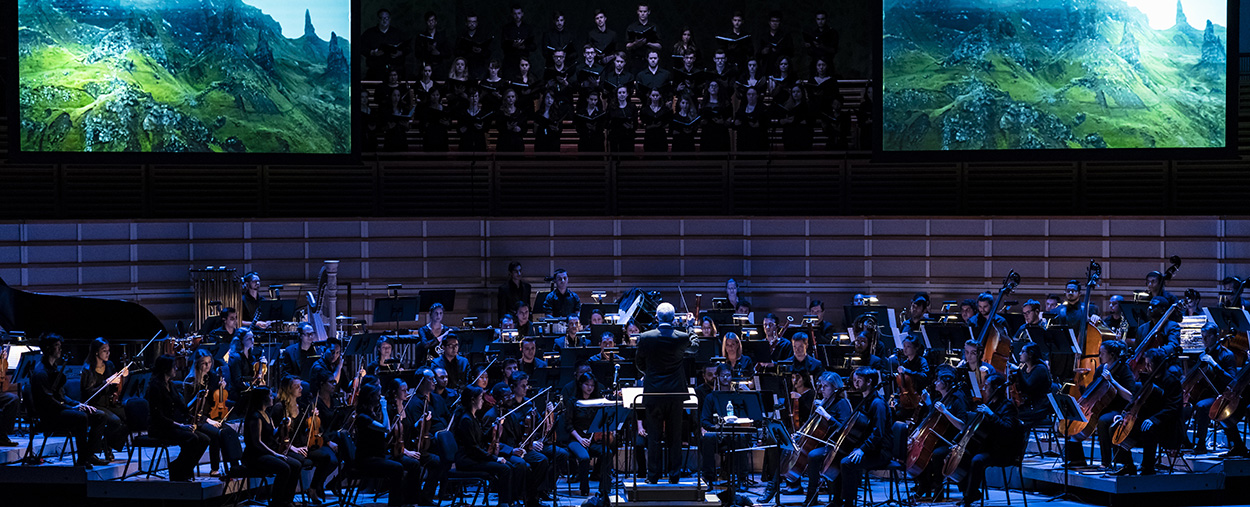 Orchestra and chorus perform live on stage