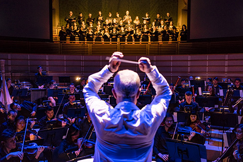 A conductor directs the orchestra during a live performance