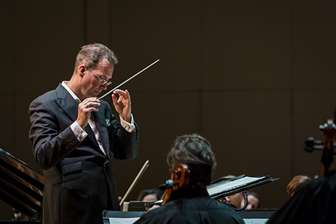 A director directs the orchestra during a live performance